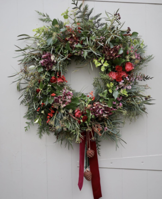 An evergreen explosion with red berries and ribbon. Fresh Christmas wreath by Tangle and Thyme, Essex