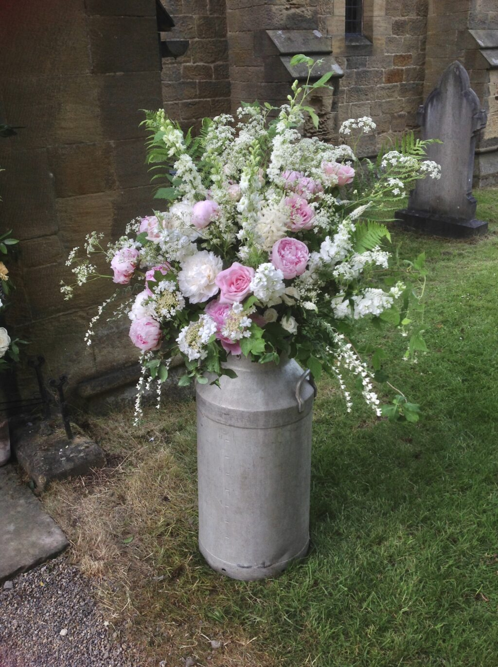 Wedding flowers - a milk churn outside the church is packed with scents from pink roses, white peonies and stocks, and overflows with frothy white cow parsley and ammi for a wildflower style church wedding