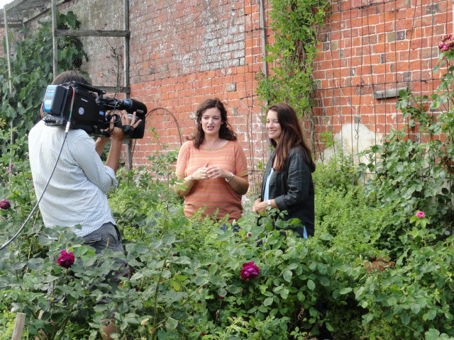 Rachel de Thame discusses cut flower growing for the British Garden Revival programme with Catkin's Rachel Petheram in the walled garden at Doddington Hall. A cameraman films them chatting in front of a beautiful brick wall with old rambling roses scrambling up it.