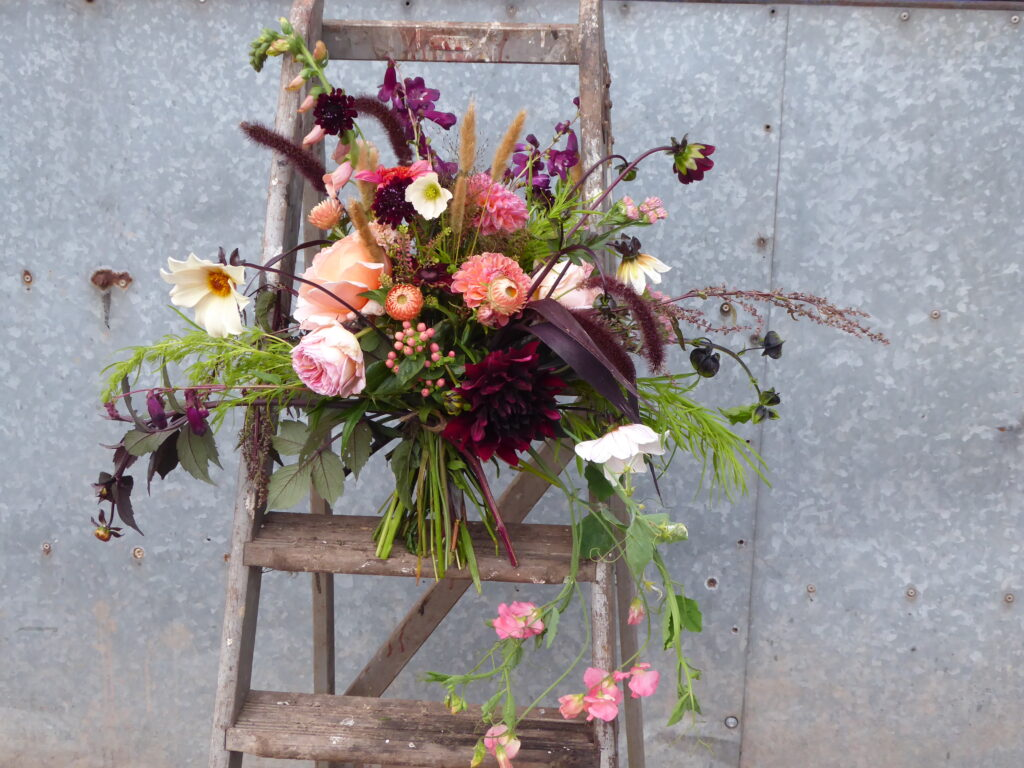 A gorgeous bouquet of locally grown British flowers by Quirky flowers, Staffordshire, stands on an old stepladder. Full of scented roses, dahlias, grasses and unusual seasonal ingredients.