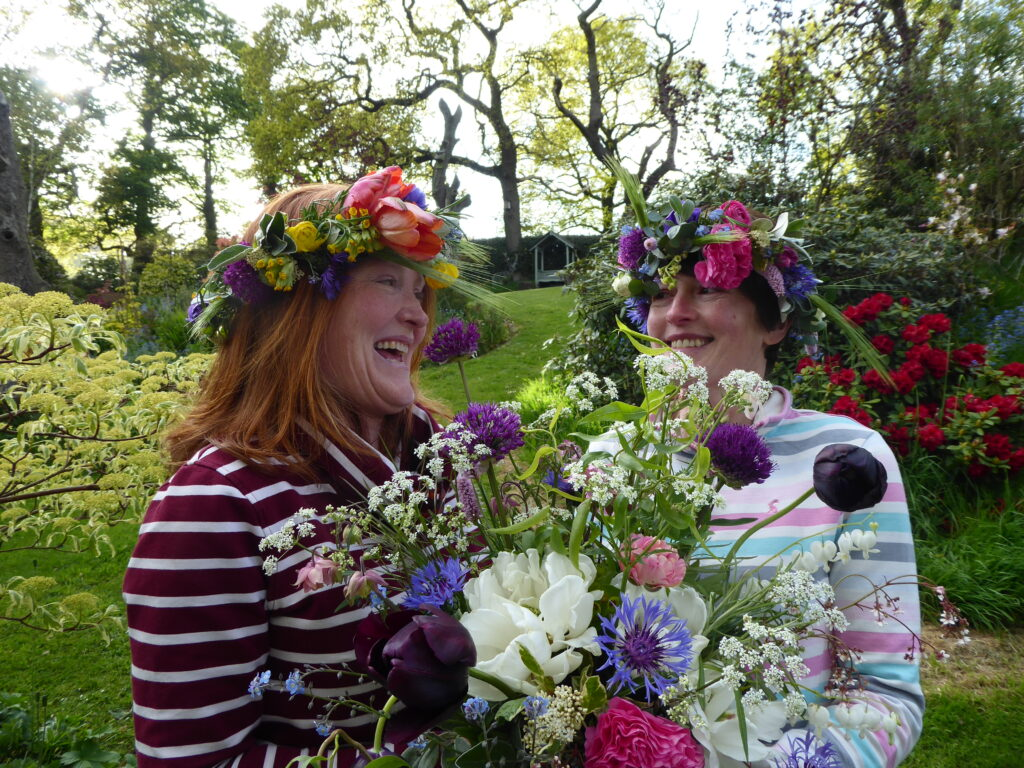 Pam of Quirky Flowers laughs in the garden with her sister at a flower crown workshop
