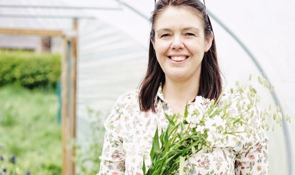 Clare of The Flower Farm holds a bunch of scented white sweet rocket as she cuts British flowers in her polytunnel for her wedding work.