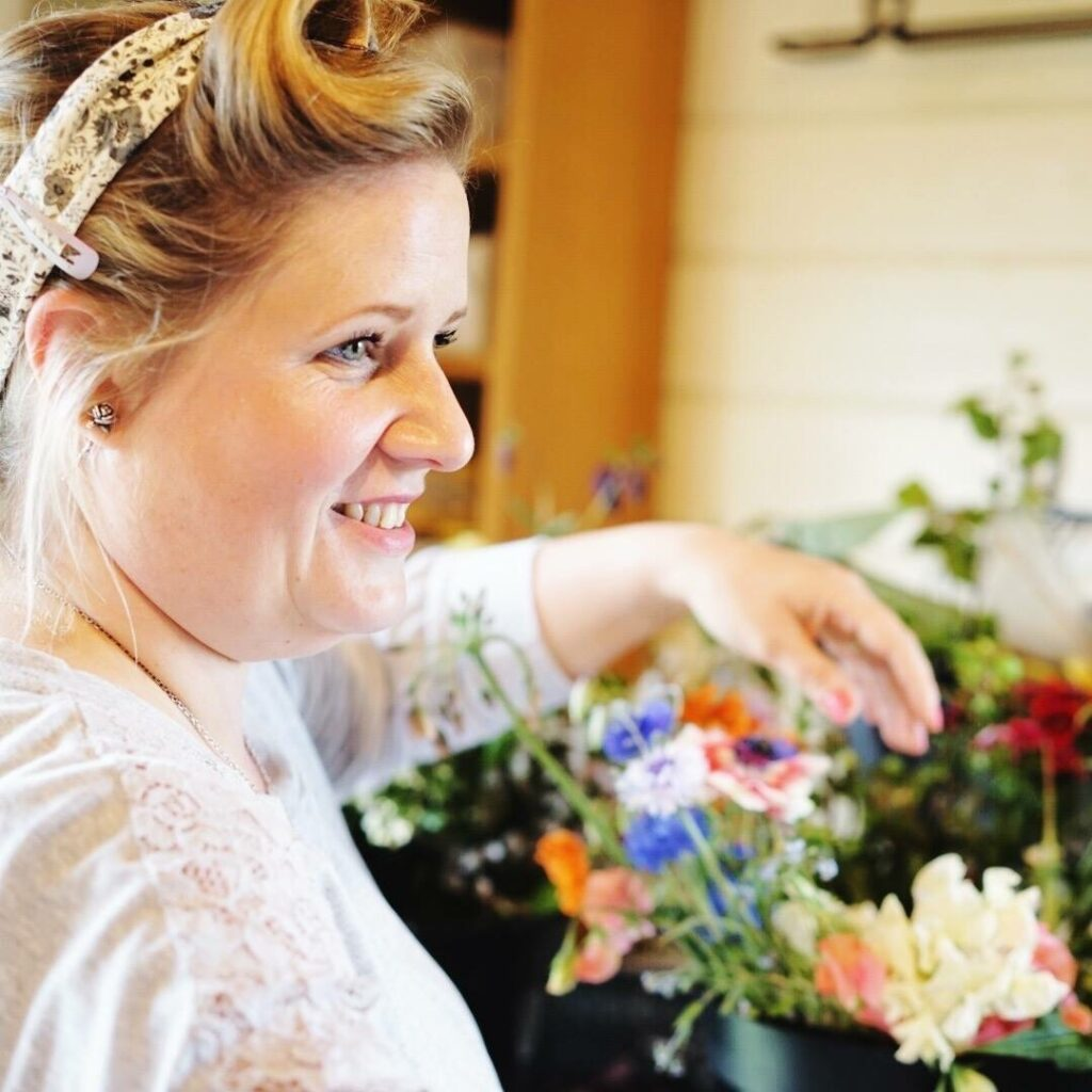 Alison of The Flower Farm smiles as she prepares bridesmaid and bridal bouquet for a wildflower style wedding.