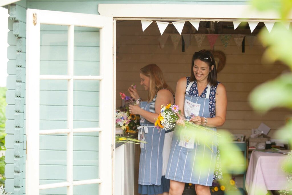 Early members of Flowers from the Farm, Clare and Alison of The Flower Farm at work, laughing together whilst making wedding flowers in her home studio in Burscough, Lancashire.