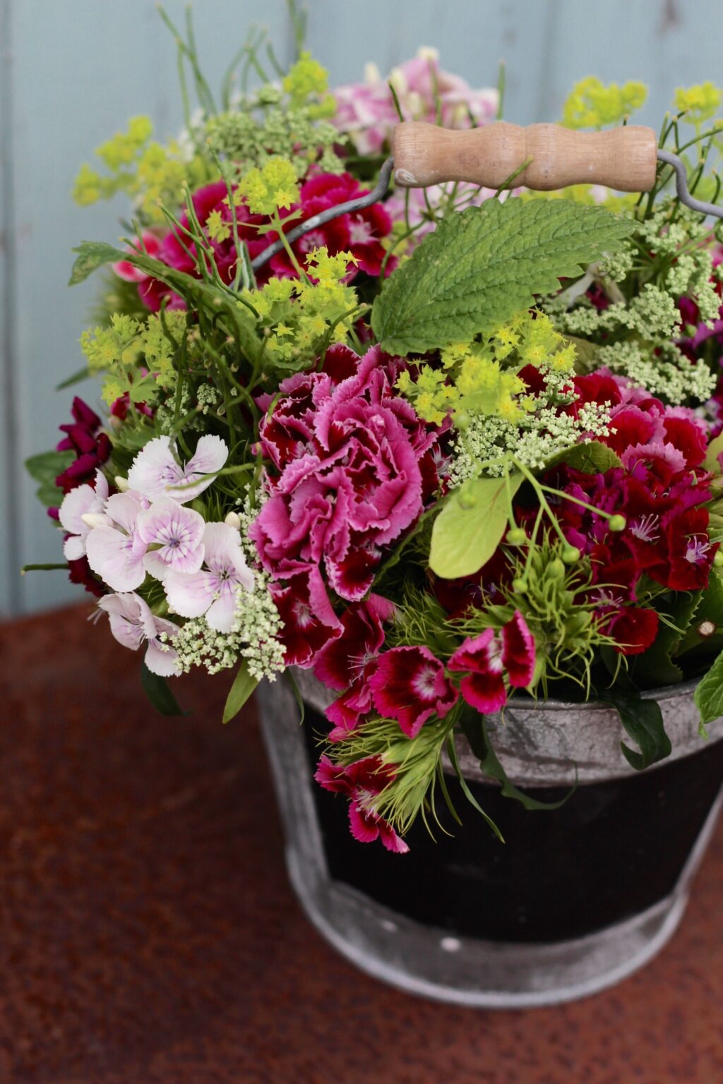 These posies of scented sweet william in a range of rich pinks, are brightened with the vivid greens of lady's mantle and delicously perfumed lemon balm leaf. Photo: Tuckshop Flowers