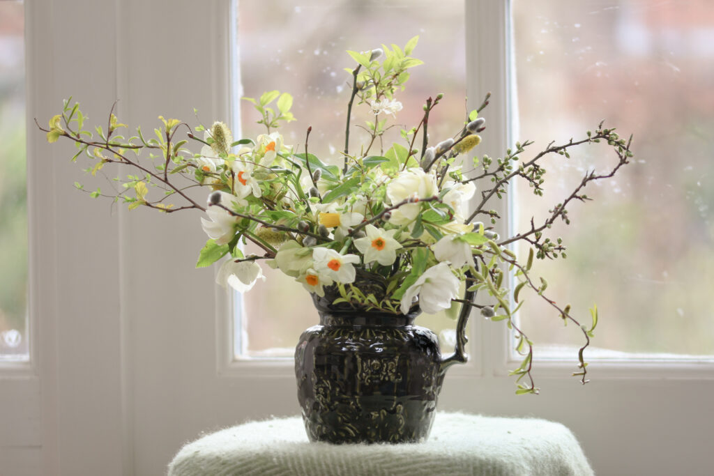 A dark green ceramic jug packed with seasonal spring flowers: narcissi, hellebores, pussy willow and bursting buds of bright green foliage.Tuckshop Flowers