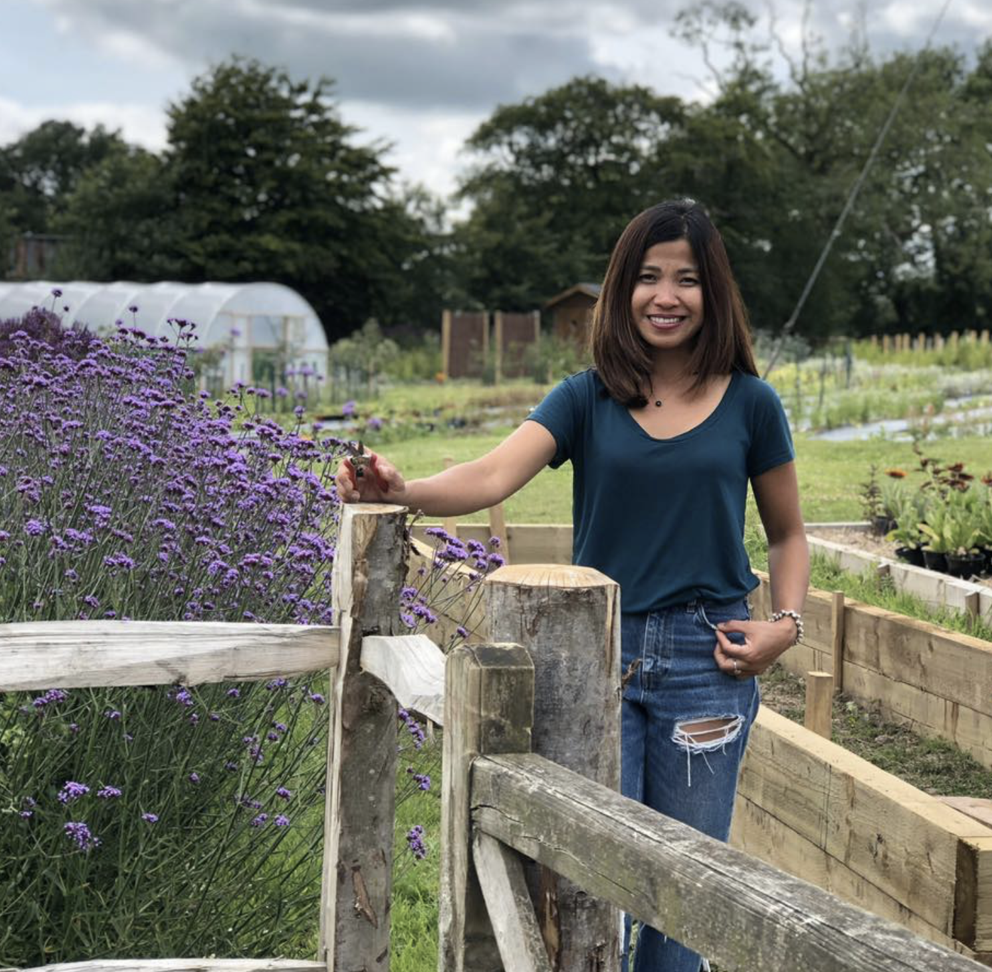 Aizel Finch of Yalham Hayes Flower Farm stands smiling by a fence on her flower plot with purple verbena bonariensis billowing out of the borders in high summer.
