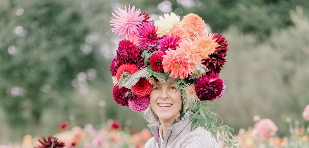 Justdahlias Philippa wears the flowers that she's obsessed with piled high in a towering hat made of richly coloured blooms.