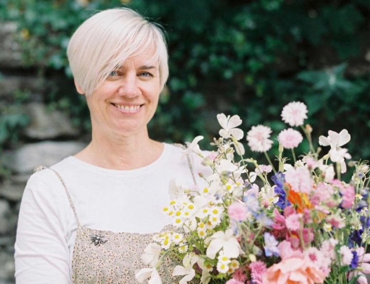 Kirsten of Henthorn Farm Flowers holds a bucket of British cut flowers brimming with scented roses and wildflower style cottage garden varieties.