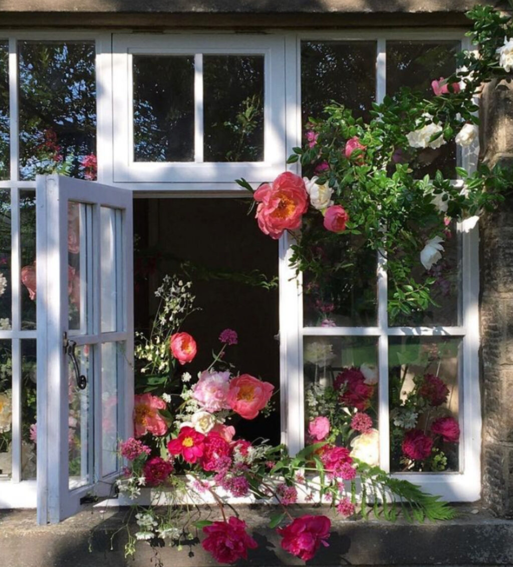 Roses clamber around the window on a stone built house, and an arrangement made with peonies and red valerian cascades through the open window. Photo: Beamsley Blooms.
