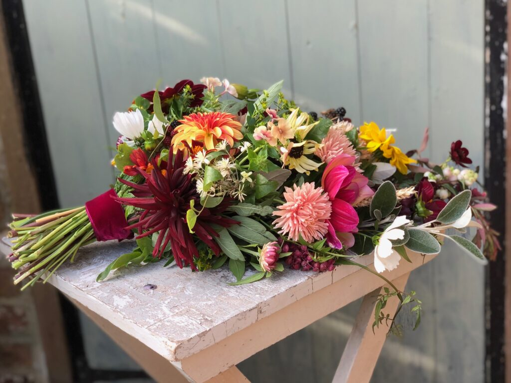 Colourful autumn sheaf with dahlias by Blackbird Garden sits on a wooden table in front of a painted door.