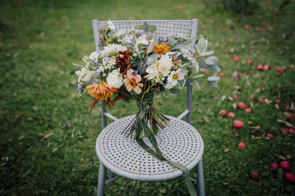 A pastel bouquet with pops of orange by Camomile and Cornflowers stands on a metal chair on the grass. Photo by Dearest Love Photography.