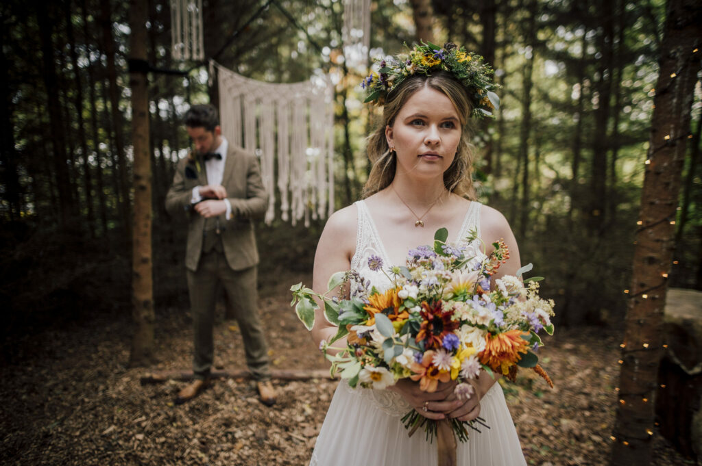 A bride wearing a wildflower flower crown for a woodland wedding holds a bouquet of vibrant summer flowers. Camomile and Cornflowers. Photo Dearest Love Photography.