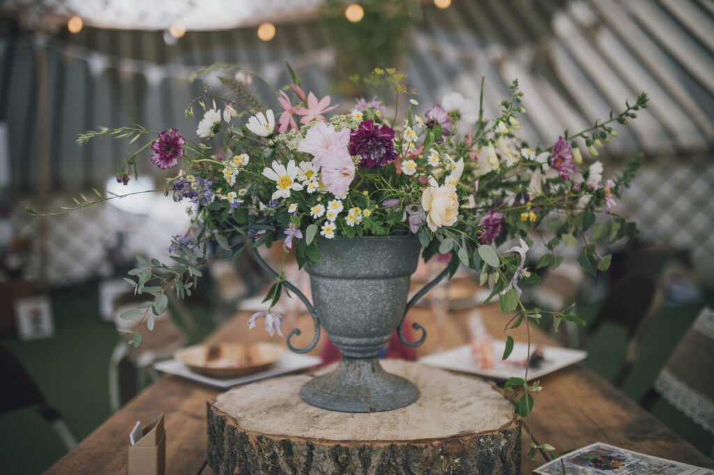 A wedding urn filled with pastel summer flowers stands on a log slice in a marquee. Camomile and Cornflowers. Photo by Dearest Love Photography.