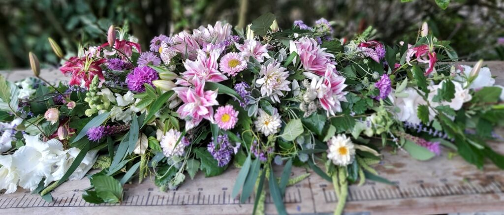 A pink summer coffin spray by Camomile and Cornflowers rests on a table.
