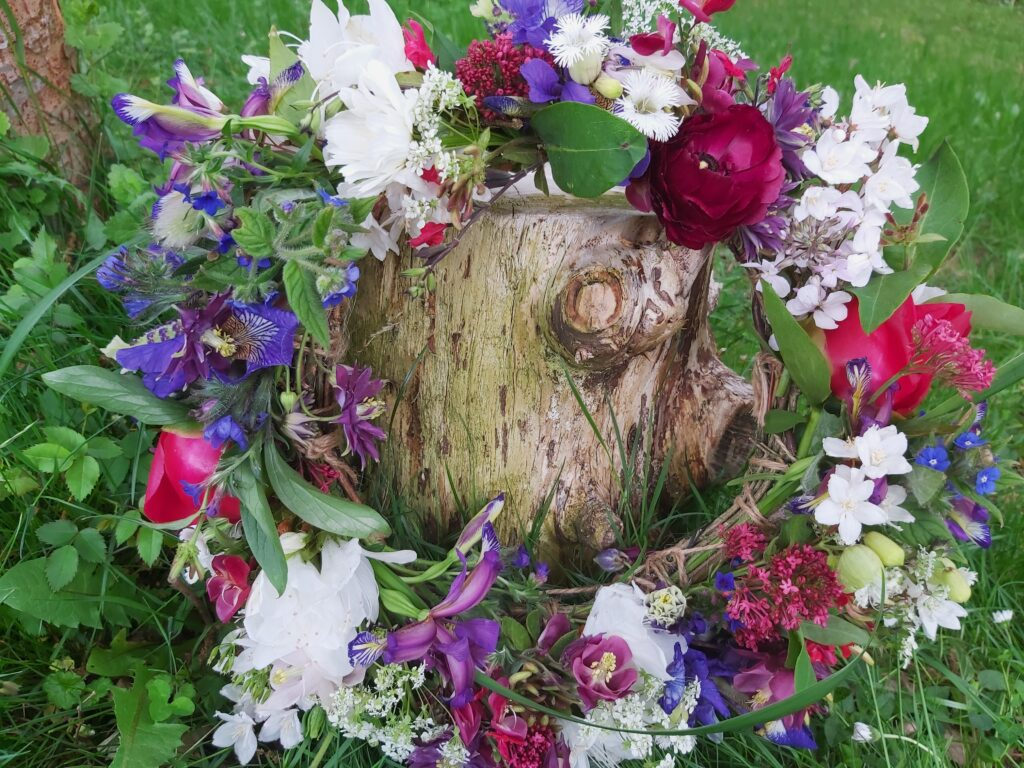 A flower crown filled with blue iris, red ranunculus, white sweet rocket and mock orange blossom, columbines and tiny sweetly scented white pinks sits on the grass, leaning against a tree stump in the flower field at Camomile and Cornflowers.