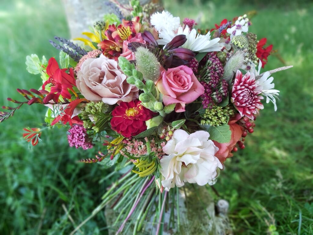 A vibrant bouquet of summer flowers in a loose wildflower style by Camomile and Cornflowers.