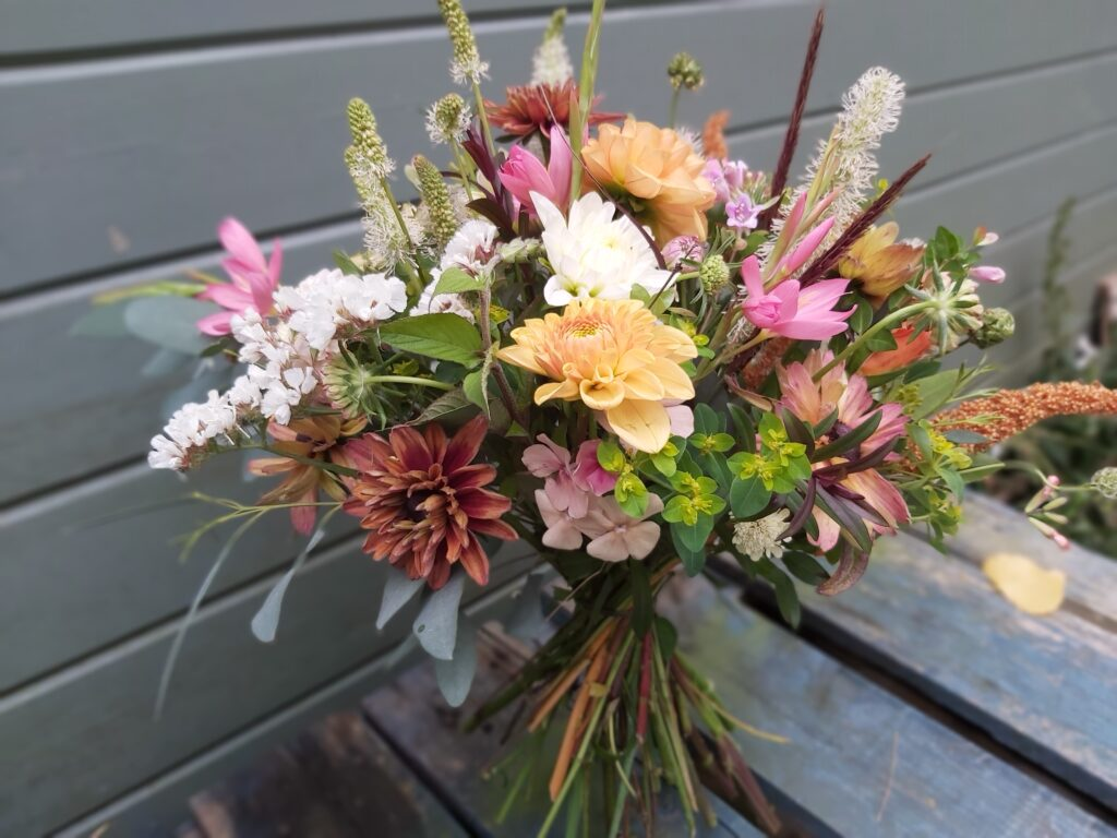 A late summer hand tie in autumnal shades with fluffy plumes of grass