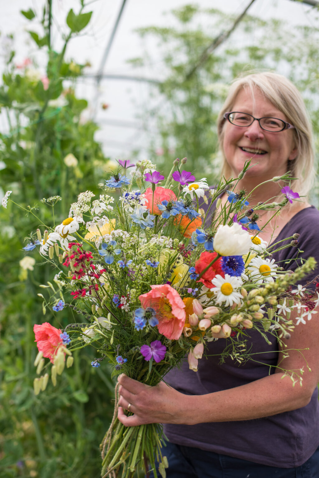 Carol' Garden owner Carol Siddorn smiles holding a bright bouquet of late spring flowers featuring foxgloves, enormous coral poppies, dog's eye daisies, cornflowers and love in a mist.