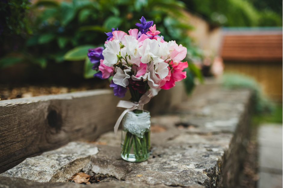A posy of freshly cut sweet peas in shades of pink, white and purple, tied with a simple ribbon stand in a jar on top of a rough stone wall. Photo: Compton Garden Flowers.