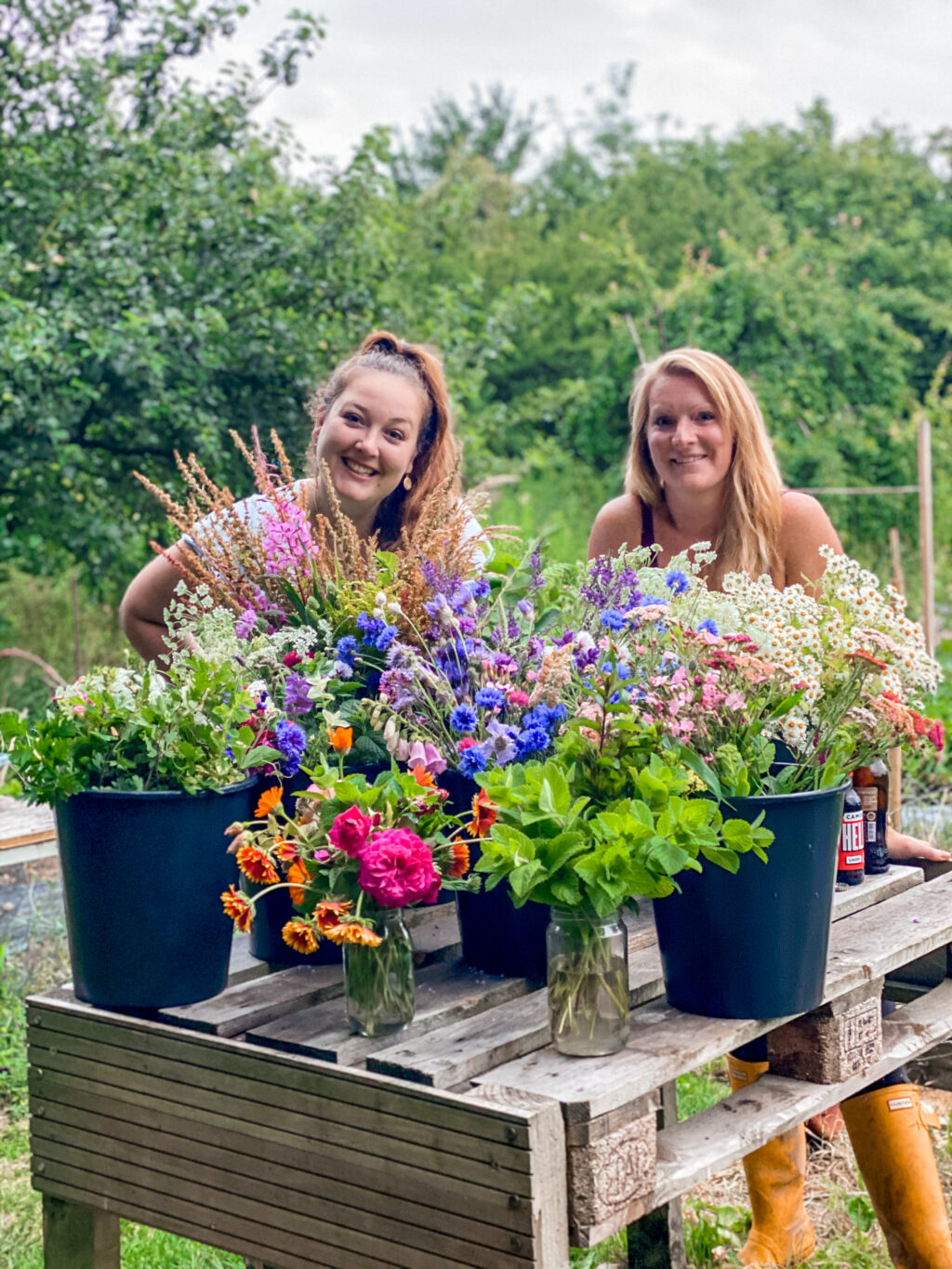 The Elworthy Flowers team survey their outdoor table filled with buckets of zesty green mint, cornflowers, tancetum daisies, orange pot marigolds and pale pink foxgloves - the best of the late spring cutting patch.
