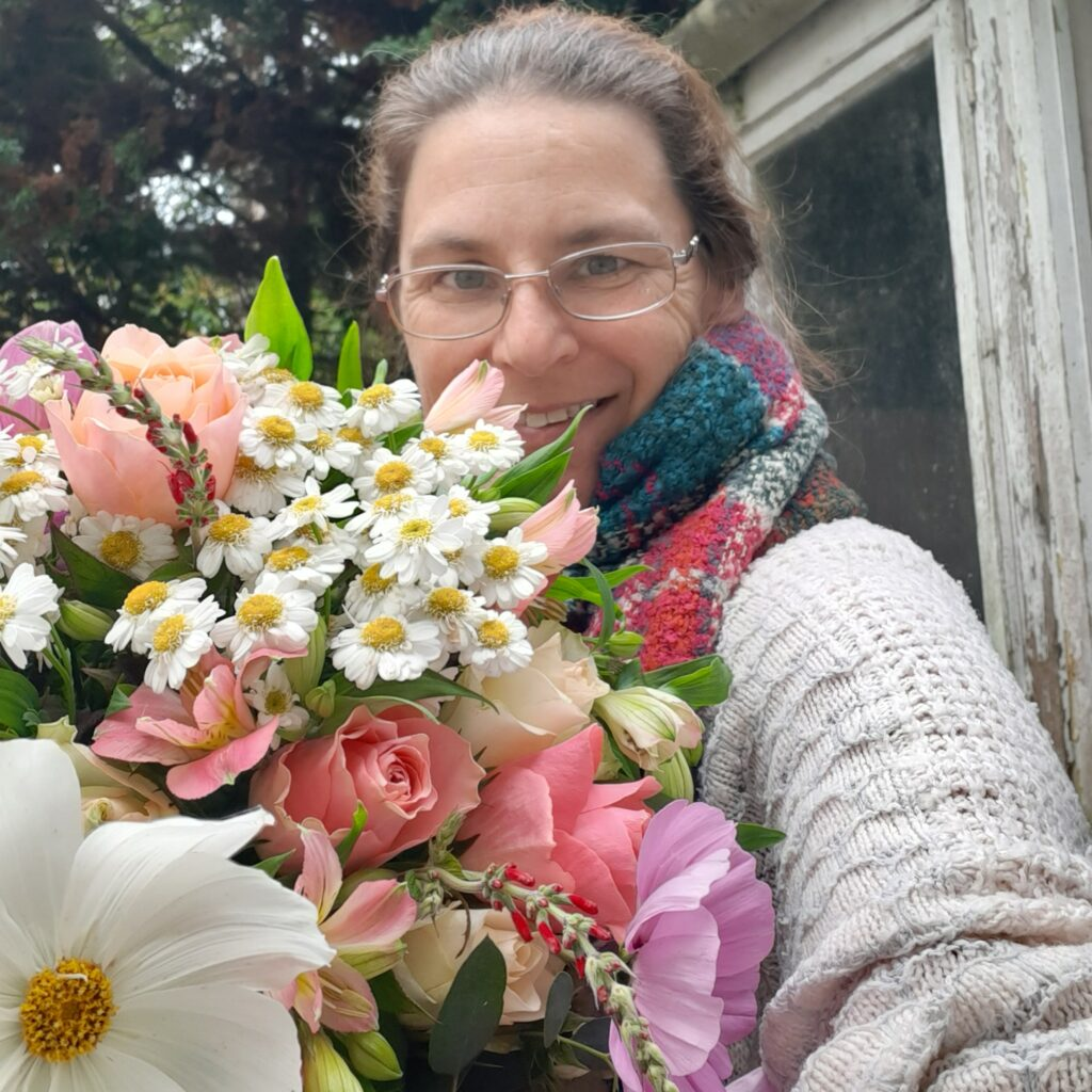 Emma holds a huge bunch of summer flowers, freshly picked from her allotment