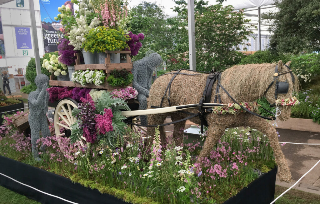 Flowers from the Farm's gold medal winning display at RHS Chelsea Flower Show. Our wire horse, Flora, adorned with dried flowers on her bridal and harness, pulls a cart laden with seasonal British cut flowers along a path of meadow flowers. Photo: Tuckshop Flowers.