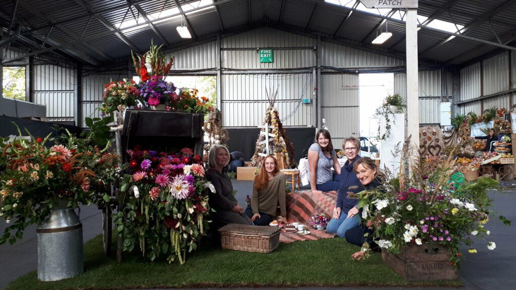 Flowers from the Farm members sit in front of their display of British cut flowers at the RHS Malvern Autumn show.