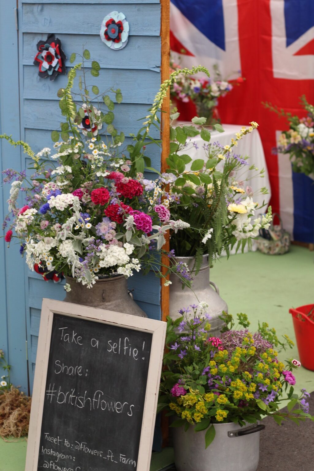 A display of British flowers in milk churns and zinc containers surround the selfie station at BBC Gardeners World Live. Made by the West Midlands members of Flowers from the Farm, the stand features a blue painted shed wall adorned with fabric flowers, and a large union jack hangs in the background.
