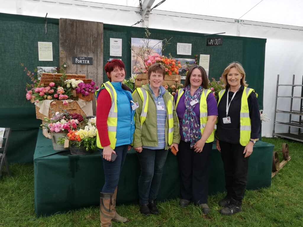 FFTF Wales members stand in front of their station themed display at RHS Cardiff which holds wicker hampers full of tulips, zinc buckets with peonies and 1930s style signage in their railway waiting room.