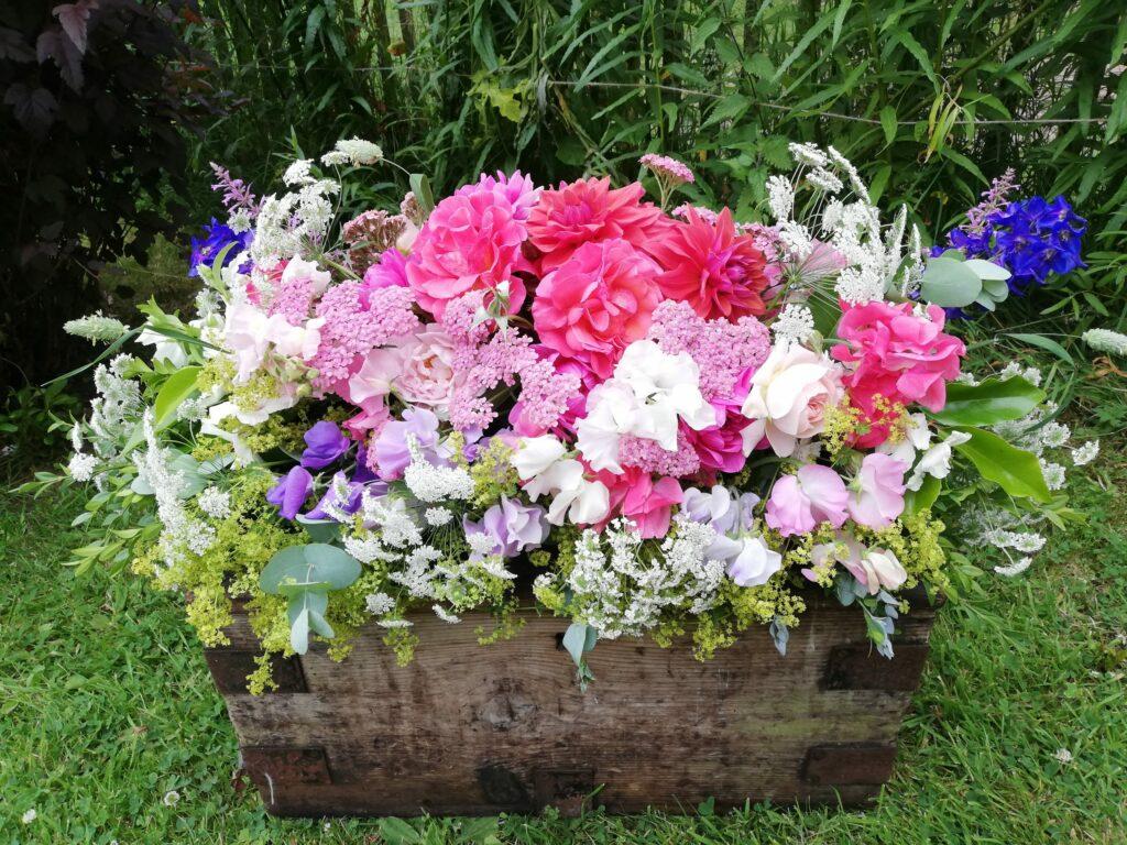 A summer casket spray of seasonal summer flowers by Farhill Flowers