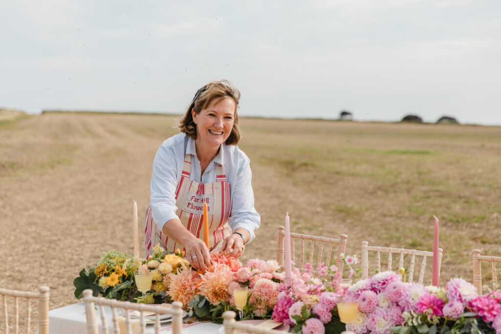 Justine of Farhill Flowers sets up a festival wedding table for an outdoor wedding with pastel dahlias and candles. Michelle Huggleston Photography.