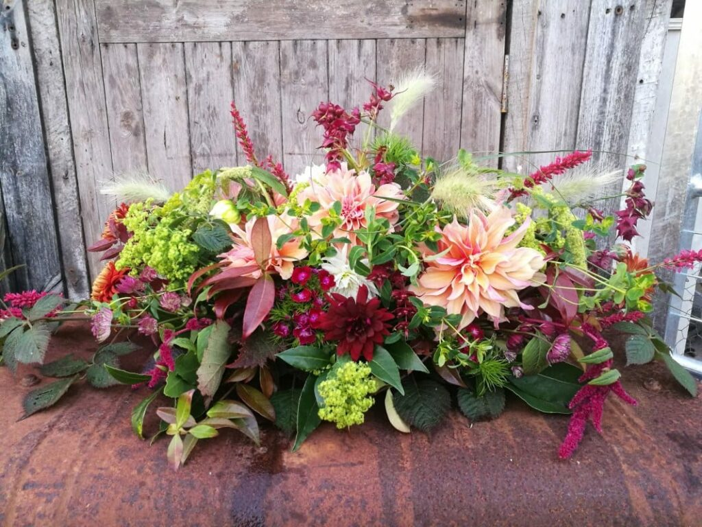 An autumn casket spray for a funeral, featuring rich dark and peachy dahlias with plumes of grass and seasonal foliage.