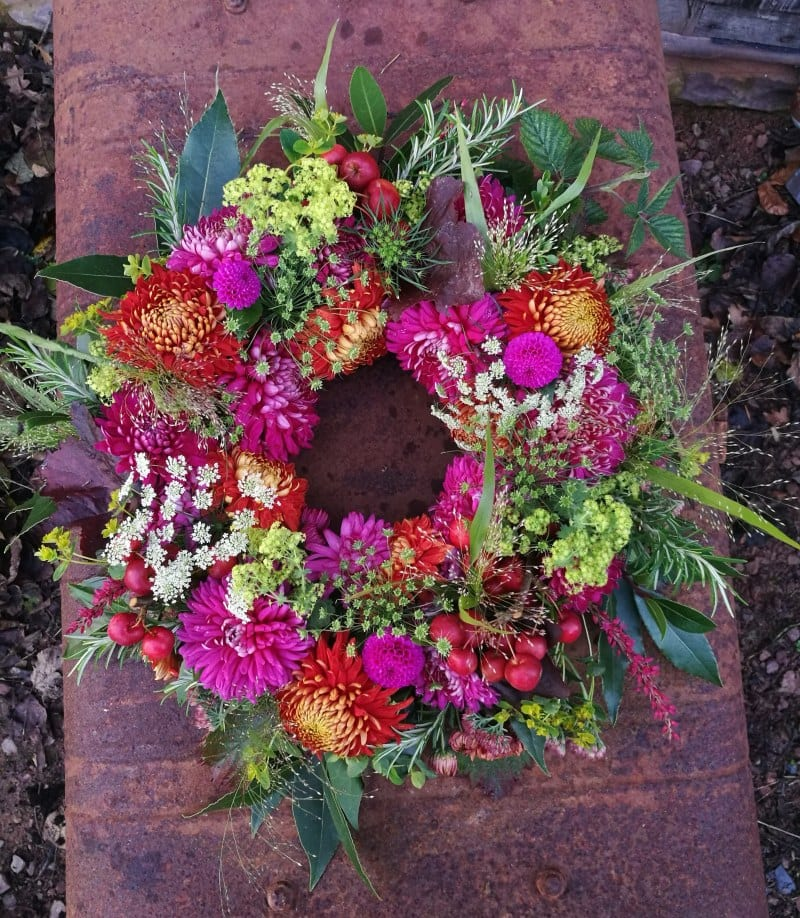 A bright autumn funeral wreath with chrysanthemums and dahlias by Farhill Flowers.