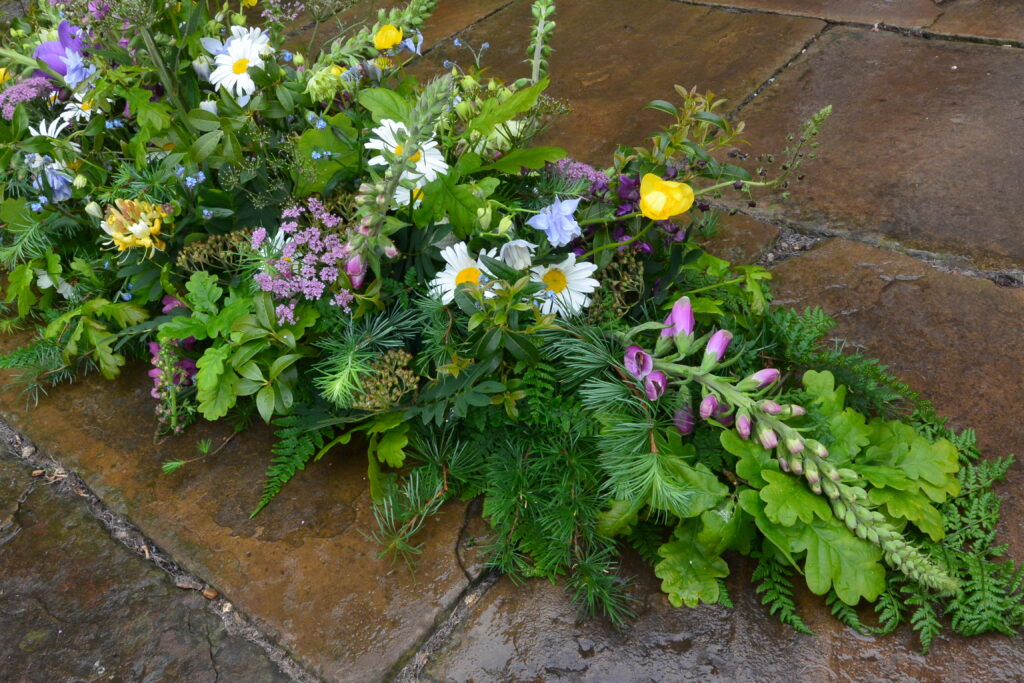 early summer funeral flowers with daisies and foxgloves by Field House Flowers