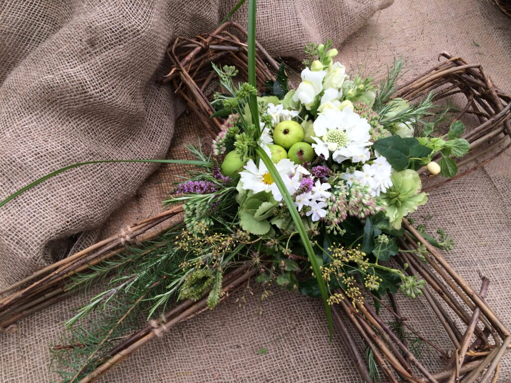A natural woven cross decorated with grasses, flowers and crab apples by Field House Flowers, Yorkshire.