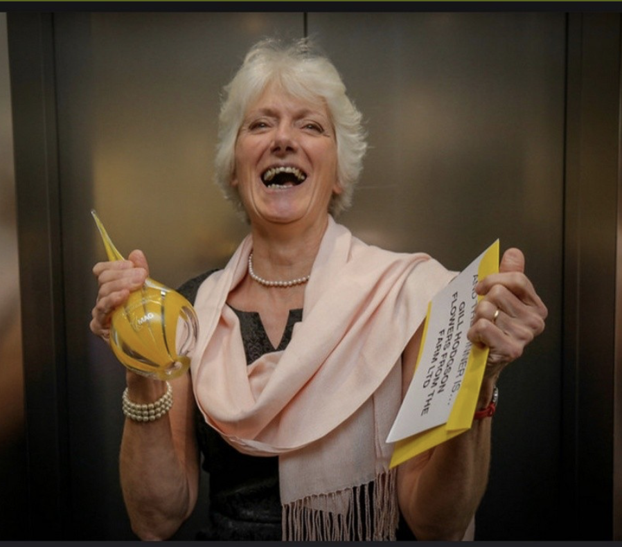 Gill holding a glass trophy and bottle of champagne as she celebrates being named Mentor of the Year in the Northern Powerhouse Awards.