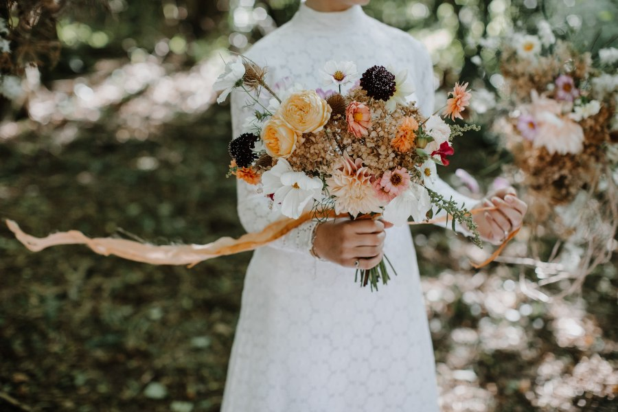 A romantic autumn bouquet with dahlias and dried hydrangeas with floaty silk ribbon held by a bride. Botanical Yard.