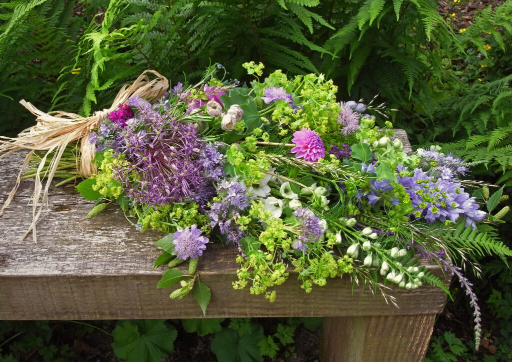 A natural tied funeral sheaf of early summer flowers by Galloway Flowers