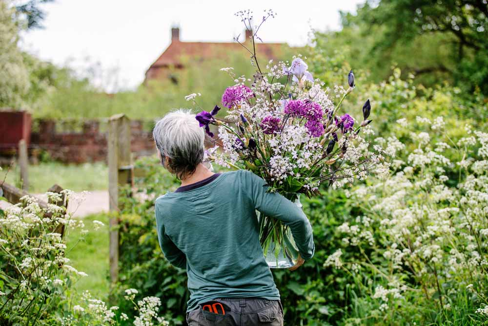 Rachel of Green and Gorgeous carries a bucket brimming with freshly cut frothy white ammi back to the workshop on her flower farm.