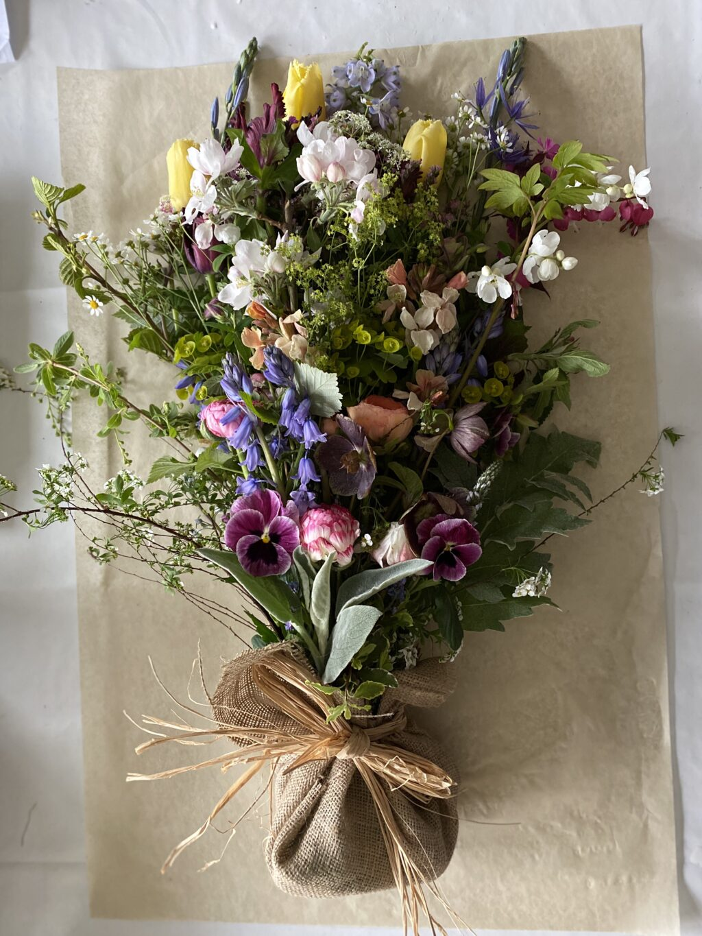 A natural funeral sheaf with seasonal spring flowers: tulips, bluebells, pansies and blossom. By Henthorn Farm Flowers.