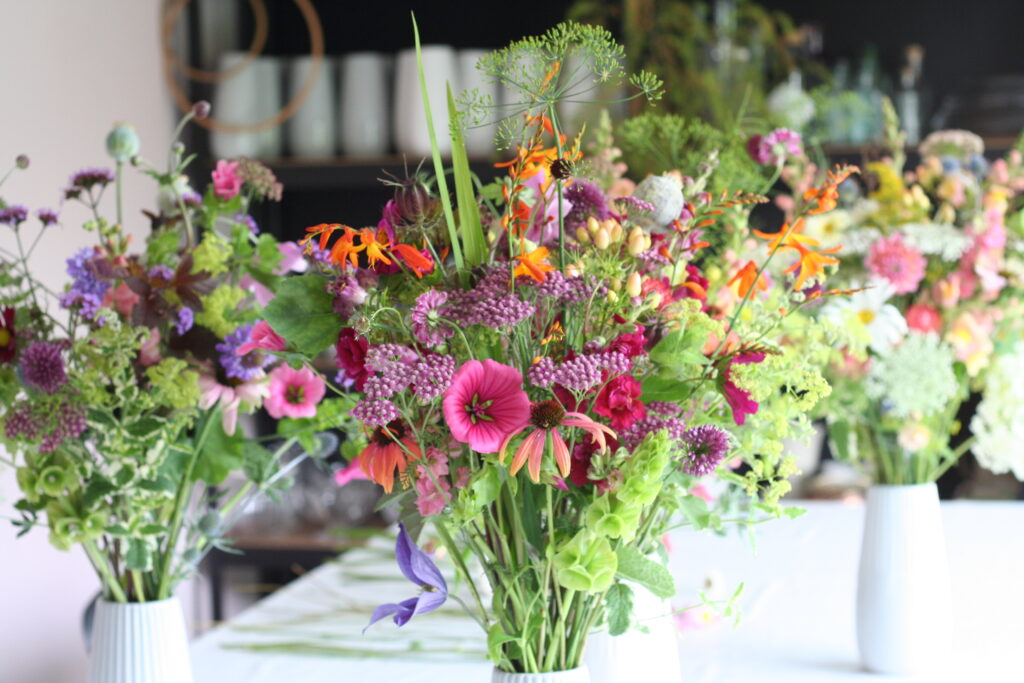 Colourful summer jugs of British cut flowers by Henthorn Farm Flowers. Pink male, orange crocosmia and vivid green bells of Ireland.