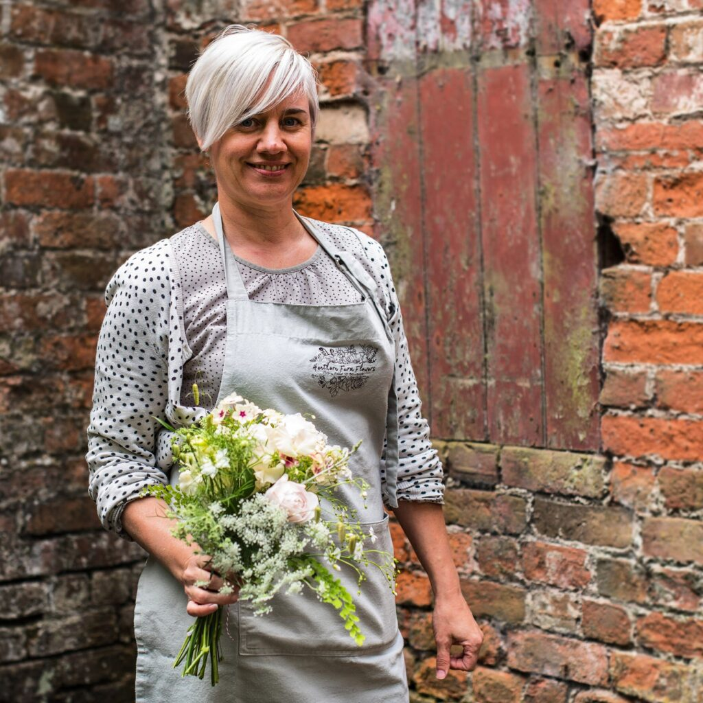 Kirsten of Henthorn Farm Flowers holds a seasonal boquuet of delicate British cut flowers - frothy Queen Anne's Lace, love-in-a-mist, snapdragons and phlox Creme Brulee. She stands against a rough brick terracotta wall as a backdrop.