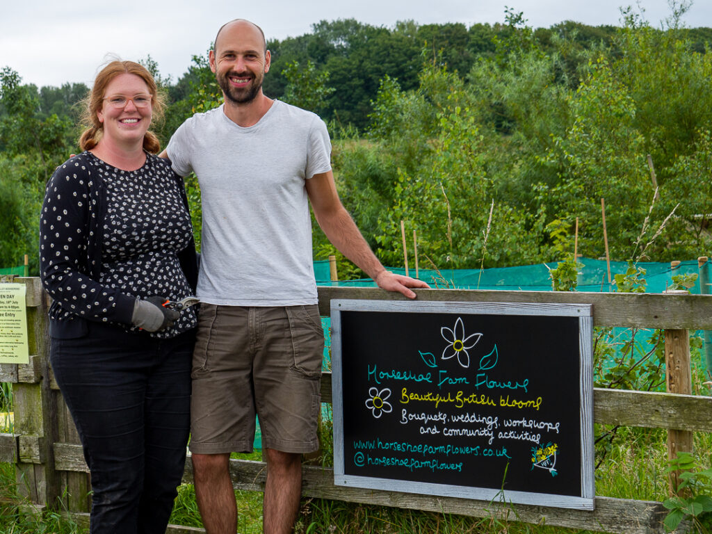 Laura and Martin of Horseshoe Flower Farm are new members of Flowers from the Farm and love working on their Lancashire flower farming business. Here they're standing proudly by the gate to the flower farm with a sign which tells the public exactly what they do