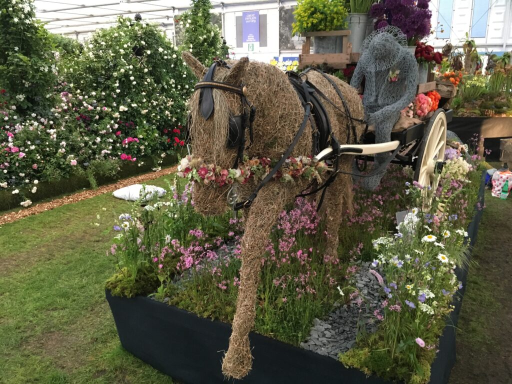 Flora the straw horse strides out at RHS Chelsea on FFTF's Going to Market display, pulling a flower laden cart along a meadow path.