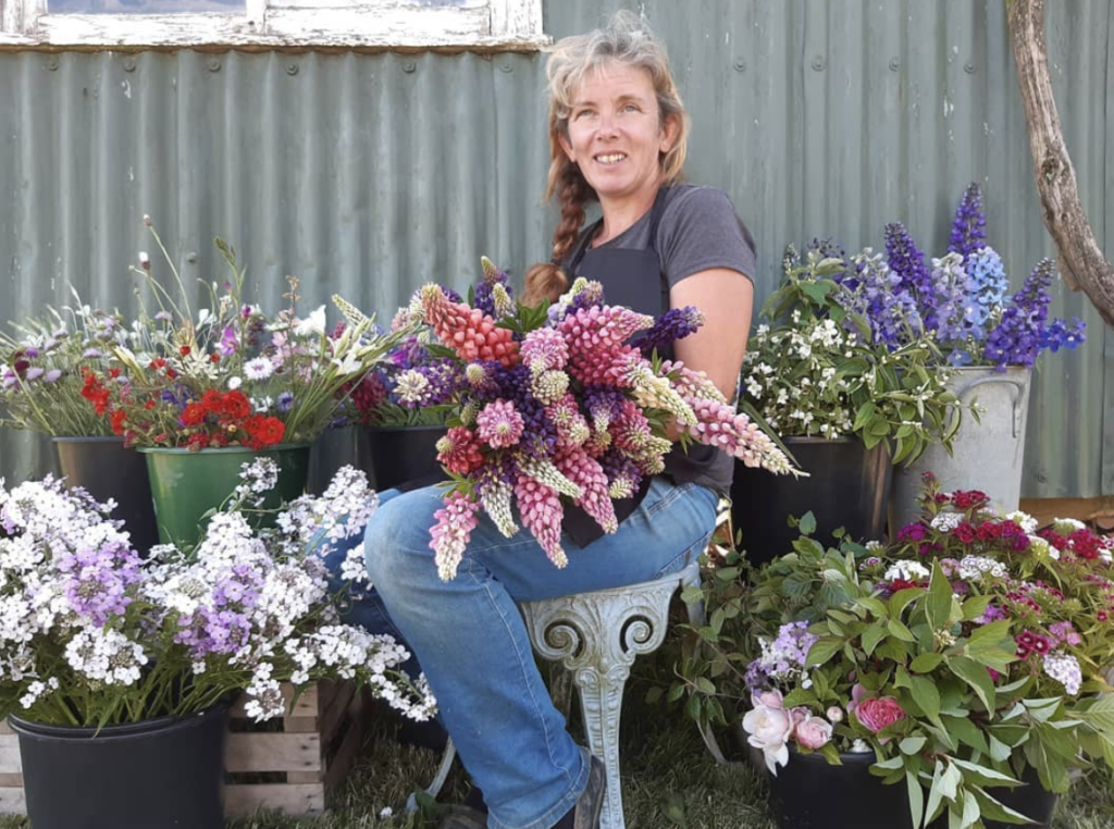 East Anglia Regional Co-ordinator Jane Hutcheon of Hay Lane flower sits amidst her buckets of glorious early summer blooms.]