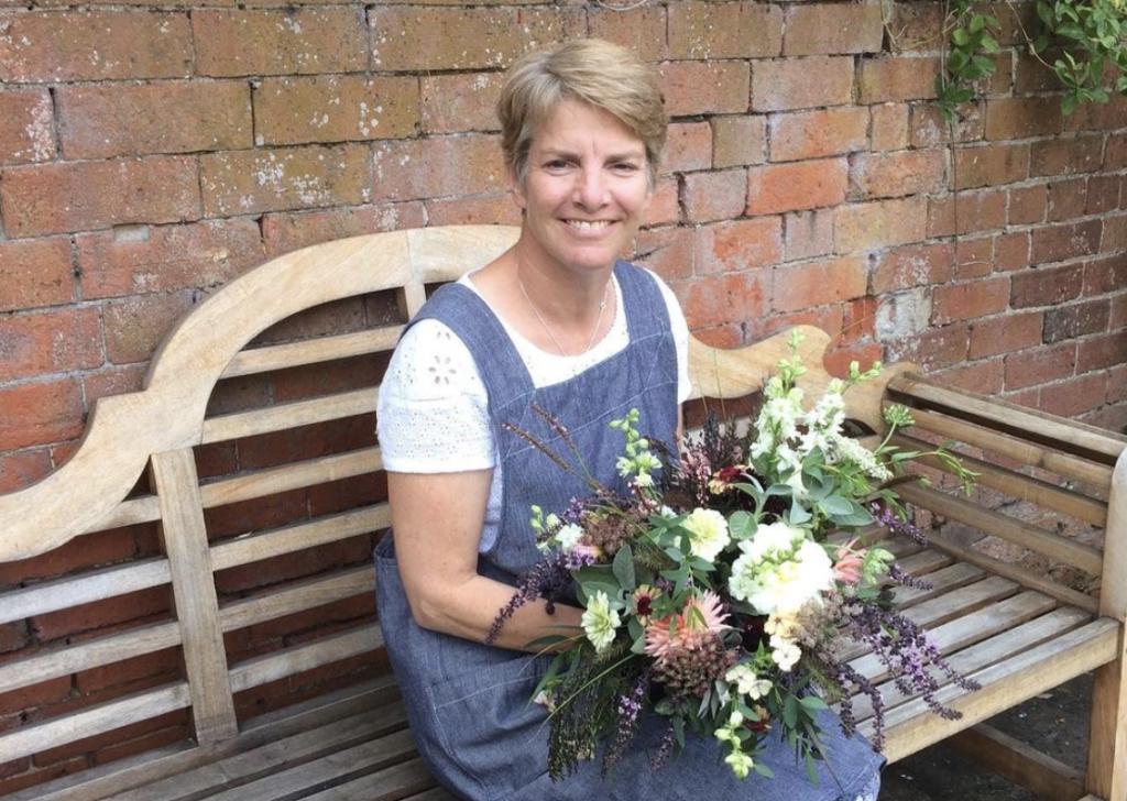 Karen Ingall, Belton Blooms sits on a bench holding flowers.