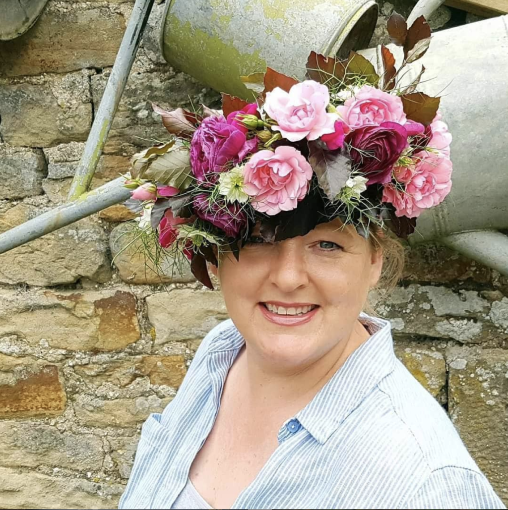 Kate Norris of Northumbrian flowers wearing an abundant flower crown with pink roses.