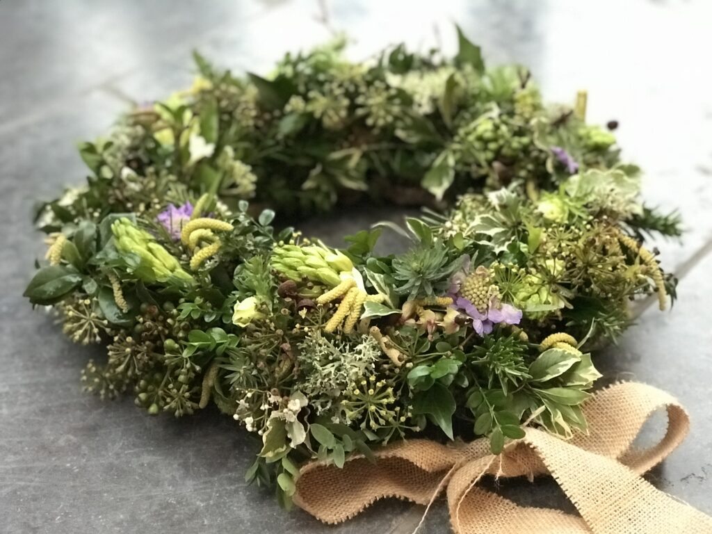 An understated woven wreath is decorated with tree ivy and catkins and a rustic hessian bow by Little Park Flowers.