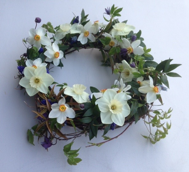 A delicate woven funeral wreath decorated with simple spring narcissi by Mayfield Flowers